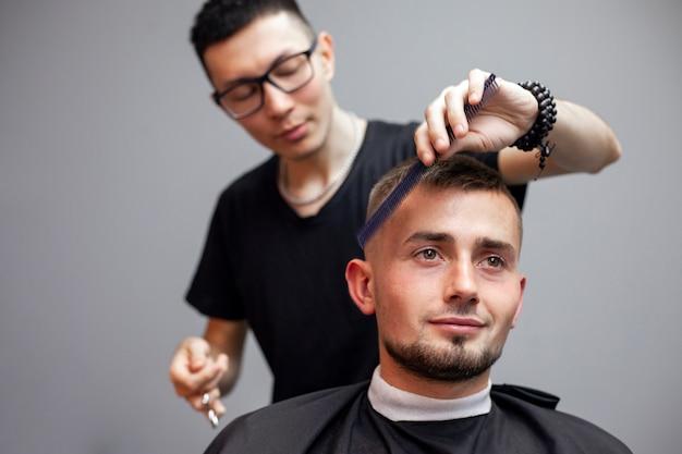 Un ragazzo si fa tagliare i capelli in un barbiere, un giovane barbiere kazako taglia manualmente con le forbici e un pettine, il maestro fa un taglio di capelli corto dal parrucchiere