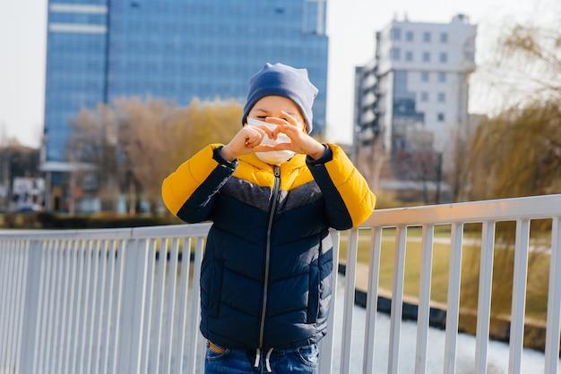 Un ragazzo si trova su uno sfondo grigio in una maschera durante una quarantena con spazio libero. quarantena nella maschera
