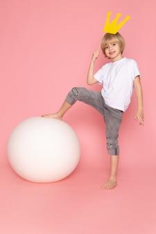 Un ragazzo sorridente biondo di vista frontale in maglietta bianca che gioca con la palla bianca sullo spazio rosa