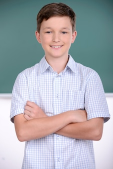 Un ragazzo sta con la mano insieme a scuola.