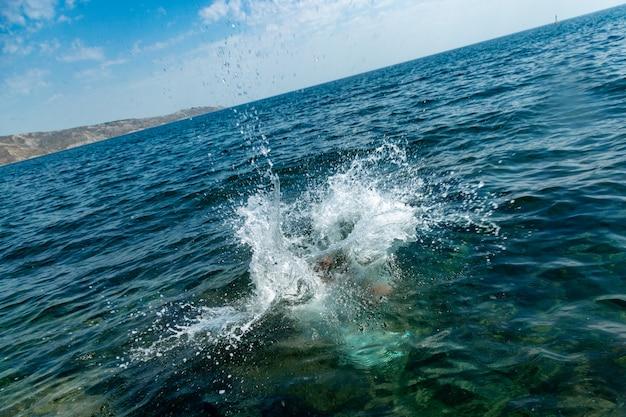 Un ragazzo sta saltando dalla scogliera nel mare con grandi spruzzi d'acqua in una calda giornata estiva. vacanze al mare. turismo attivo e ricreazione