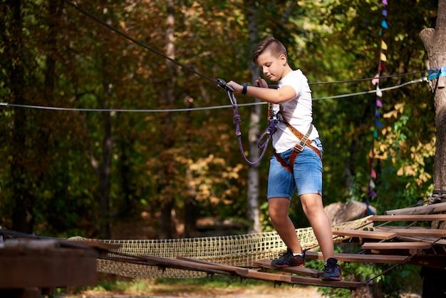 Un ragazzo supera un ostacolo in un parco di divertimenti