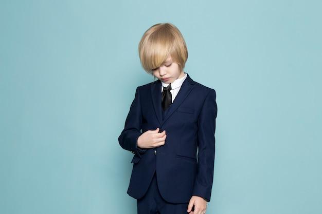 Un ragazzo sveglio di affari di vista frontale in vestito classico blu che posa modo del lavoro di affari