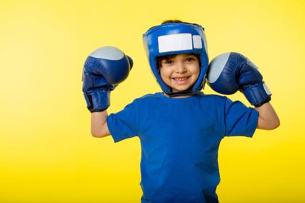 Un ragazzo sveglio sorridente di vista frontale in casco blu di pugilato dei guantoni da pugile e in maglietta blu sulla parete gialla