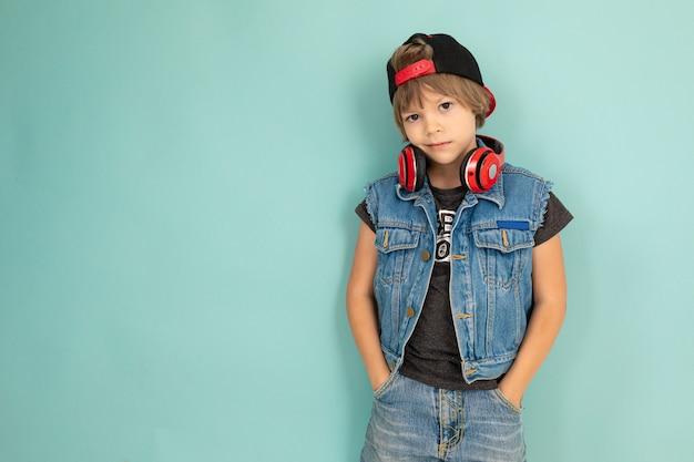 Un ragazzo tenager cool in giacca di jeans e pantaloncini, auricolari rossi, berretto nero, si trova davanti alla telecamera e tiene le mani in tasca, isolato su sfondo blu