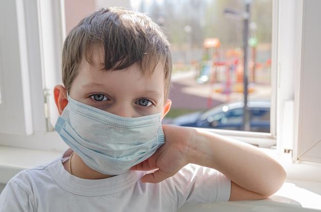 Un ragazzo triste di quattro anni con una mascherina medica si siede sul balcone e guarda fuori dalla finestra nel parco giochi. autoisolamento (quarantena) dovuto alla pandemia (epidemia) del coronovirus