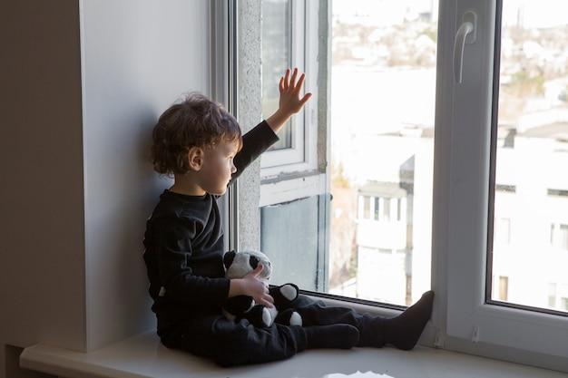 Un ragazzo triste si siede vicino alla finestra con un giocattolo di orso panda in mano durante la quarantena