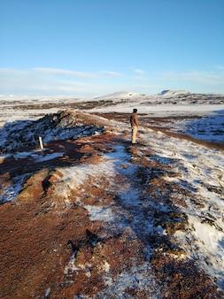 Un ragazzo turistico cammina vicino al lago kerid in inverno in islanda. incredibile paesaggio invernale dell'islanda