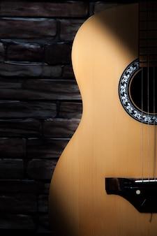Un raggio di luce cade su una chitarra acustica in piedi sullo sfondo di un muro di mattoni.