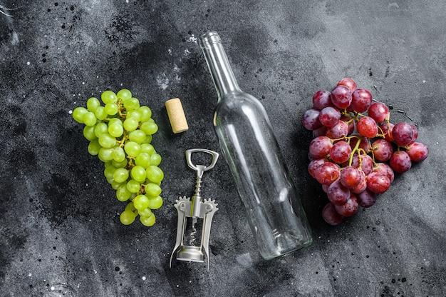 Un ramo di uva verde e rossa, una bottiglia vuota, un cavatappi e un tappo di sughero. vista dall'alto