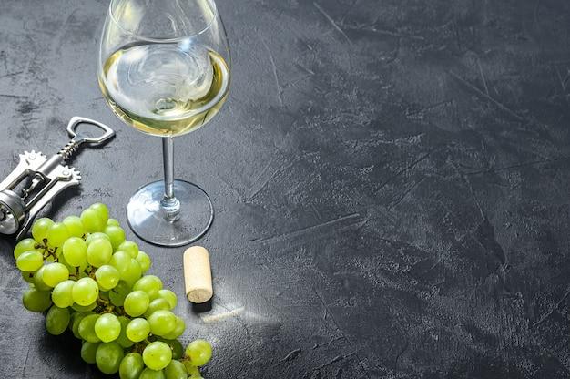 Un ramo di uva verde, un bicchiere di vino, un cavatappi e un tappo di sughero. vista dall'alto. copia spazio