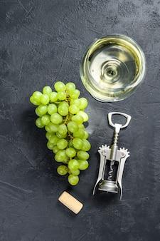 Un ramo di uva verde, un bicchiere di vino, un cavatappi e un tappo di sughero. vista dall'alto