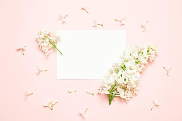 Un ramoscello di lillà si trova su uno sfondo di carta rosa.