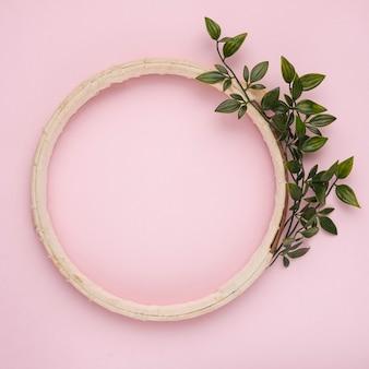 Un ramoscello verde artificiale vicino al bordo in legno cornice su sfondo rosa