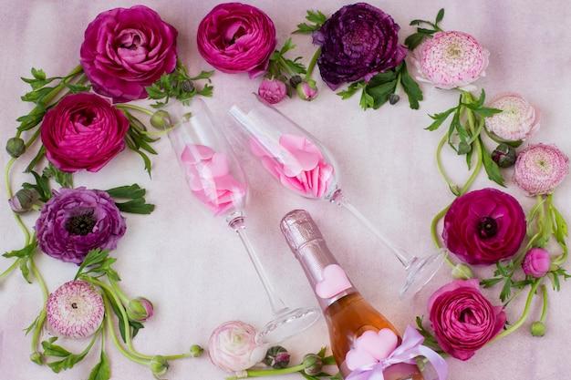 Un ranuncolo e una bottiglia di champagne e due bicchieri