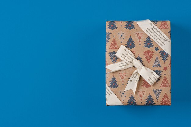 Un regalo con in carta kraft con un nastro con iscrizioni, piatto, vista dall'alto.