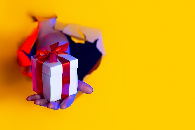 Un regalo con un fiocco rosso in mano emerge da un buco sfilacciato sullo sfondo di carta gialla, illuminato dalla luce al neon