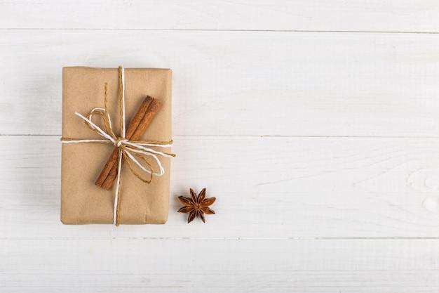 Un regalo di carta artigianale con cannella e anice stellato su un tavolo bianco.