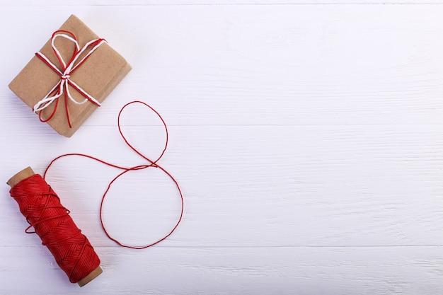 Un regalo e una corda con una figura di otto fili. concetto del giorno delle donne, insegna, spazio della copia, spazio in bianco.