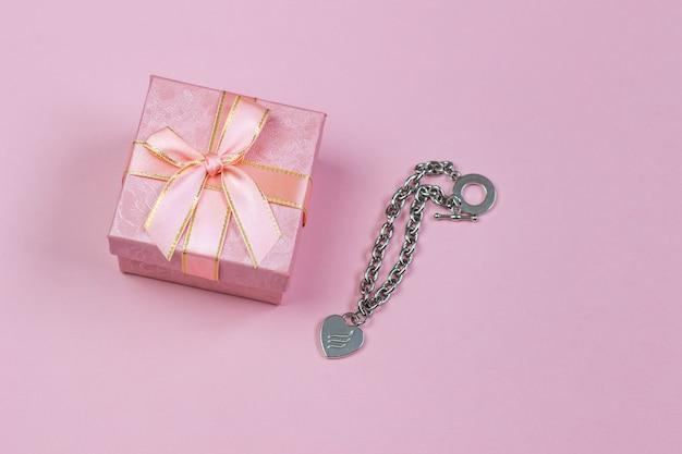 Un regalo in una bella scatola e una collana con un cuore su uno sfondo rosa