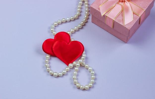 Un regalo in una scatola rosa con perle e san valentino su uno sfondo viola.