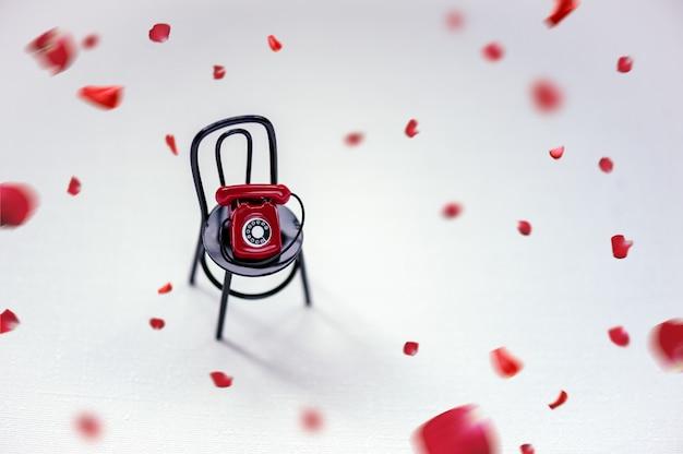 Un retro telefono rosso sulla sedia nera e luce con petali rossi. concetto di san valentino.