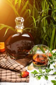 Un riflettore su un bicchiere di cristallo di brandy con frutta e verde, girato su un tavolo di legno