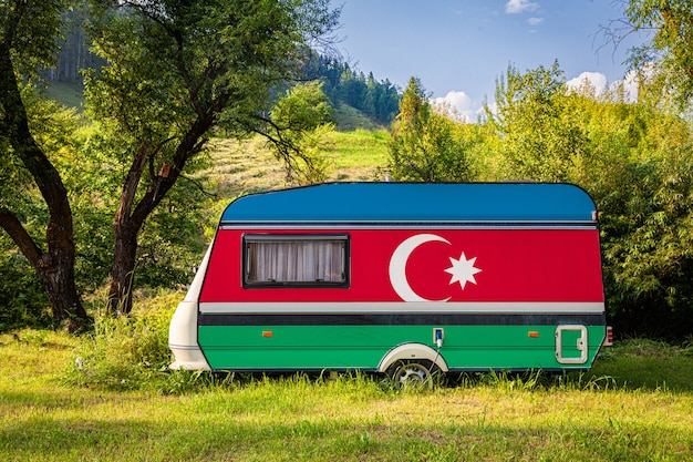 Un rimorchio per auto, un camper, dipinto con la bandiera nazionale dell'azerbaigian, è parcheggiato in una montagna.
