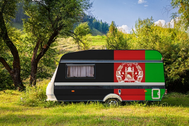 Un rimorchio per auto, un camper, dipinto nella bandiera nazionale dell'afghanistan si trova parcheggiato in una montagna.