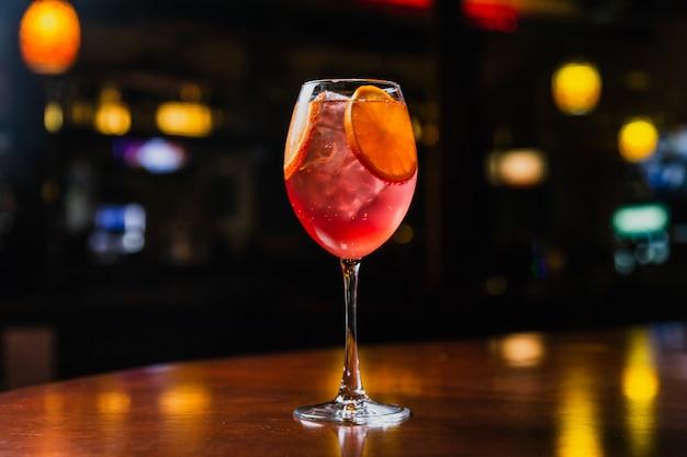 Un rinfrescante cocktail freddo con fette di ghiaccio e arancia in un bicchiere di vino