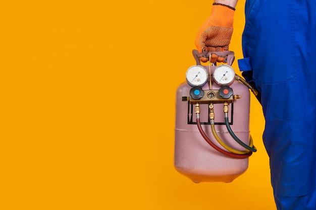 Un riparatore maschio del condizionatore d'aria tiene in mano un cilindro freon e un sensore di misurazione della pressione per il rifornimento dell'aria condizionata.