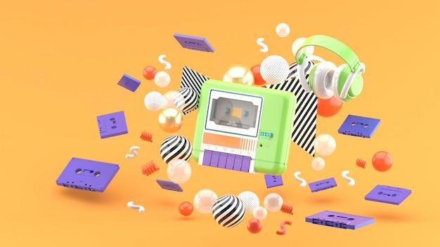 Un riproduttore di cassette verde circondato da nastri e palline colorate sull'arancia. rendering 3d.