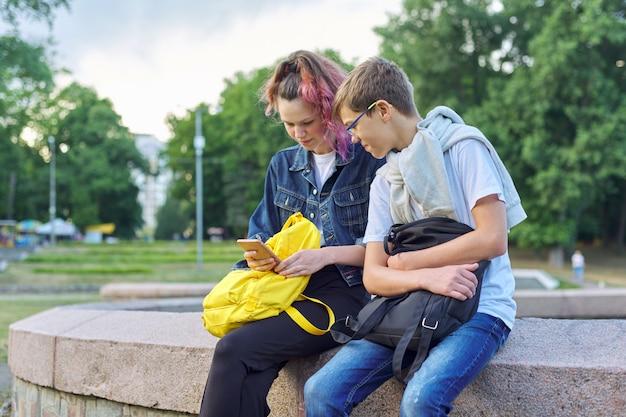 Un ritratto all'aperto di due adolescenti parlanti con lo smartphone