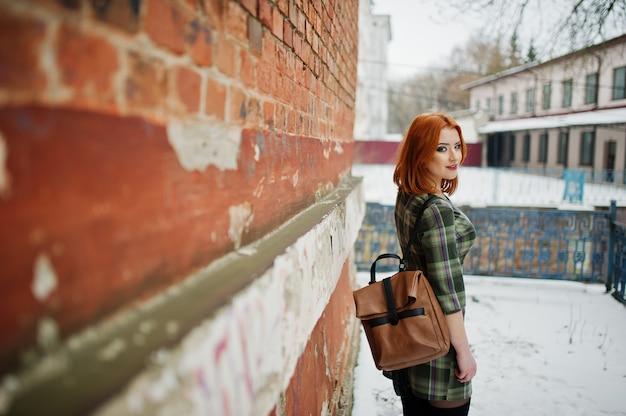 Un ritratto all'aperto di una giovane donna graziosa con i capelli rossi che indossa un abito a scacchi con zaini womany in piedi sul muro di mattoni in giornata invernale.