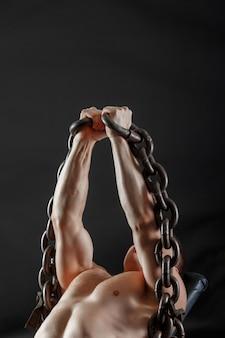 Un ritratto del culturista che solleva la catena pesante del ferro