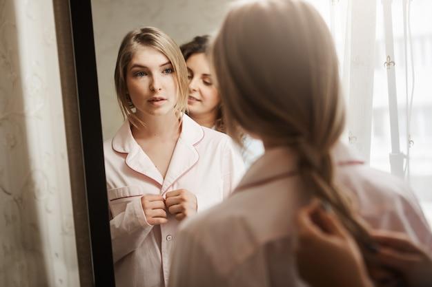Un ritratto del primo piano di due belle donne a casa. giovane bionda attraente che sta specchio vicino, cambiante i vestiti dal pigiama e aspettando mentre madre che pettina treccia. tipica mattina accogliente in famiglia