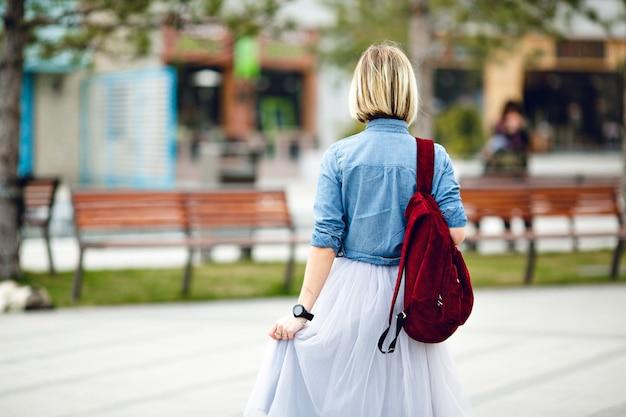 Un ritratto della parte posteriore di una ragazza con zaino marsala