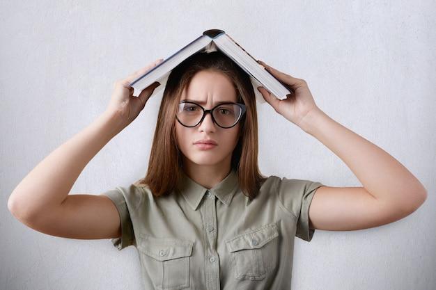 Un ritratto di alzato di bella giovane studentessa con gli occhiali sul muro bianco che tiene il suo libro sopra la sua testa stanca di leggere