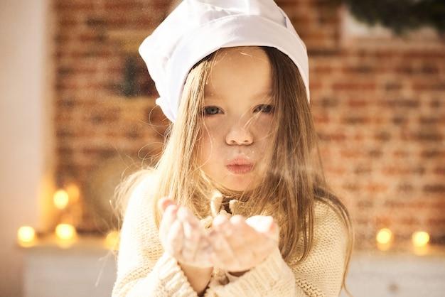 Un ritratto di bella bambina che soffia la farina in cucina