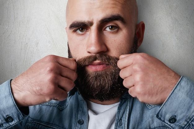 Un ritratto di close-up di bell'uomo calvo con folte sopracciglia nere, barba e baffi, occhi scuri che indossano una camicia di jeans casual