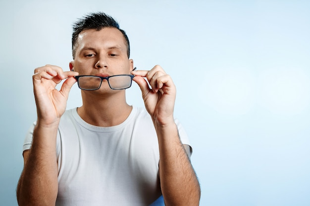 Un ritratto di close-up di un uomo che si raddrizza gli occhiali con le mani.
