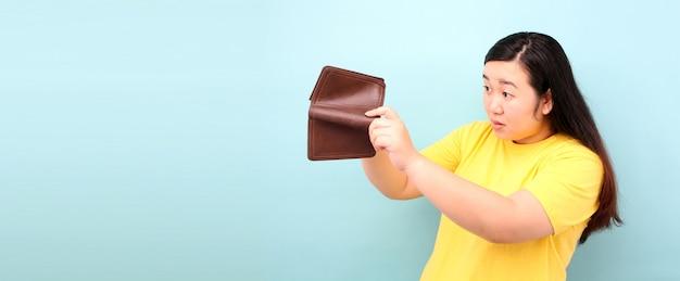 Un ritratto di close-up di una donna senza parole scioccata e sorpresa in asia, in possesso di un portafoglio vuoto su sfondo blu in studio