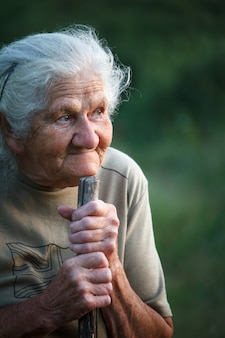 Un ritratto di close-up di una vecchia con i capelli grigi che sorride e guarda in alto, appoggiando il mento su un bastone come se camminasse con un bastone, faccia in rughe profonde