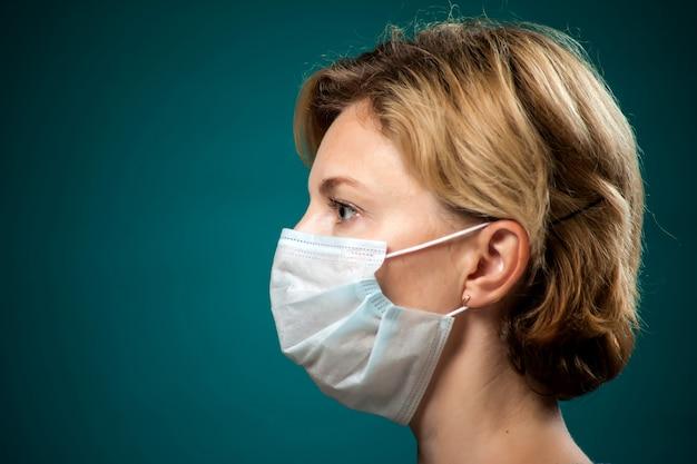 Un ritratto di donna con i capelli corti e biondi con maschera medica. concetto di persone, medicina e assistenza sanitaria. protezione da coronavirus