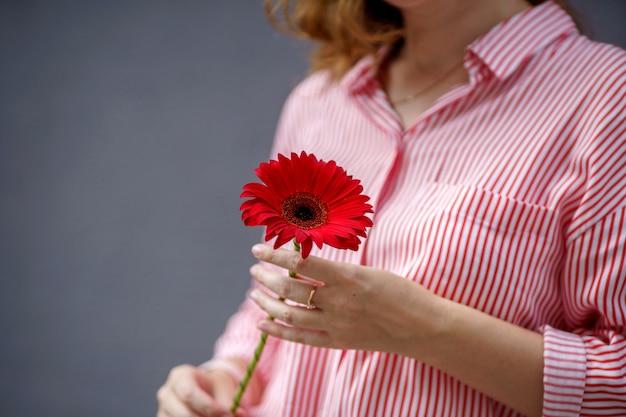 Un ritratto di donna dai capelli rossi in camicia a righe con fiore rosso nelle sue mani