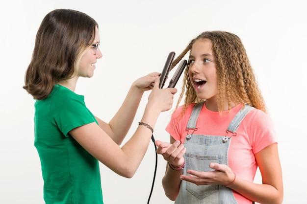 Un ritratto di due amiche adolescenti che fanno acconciatura a casa