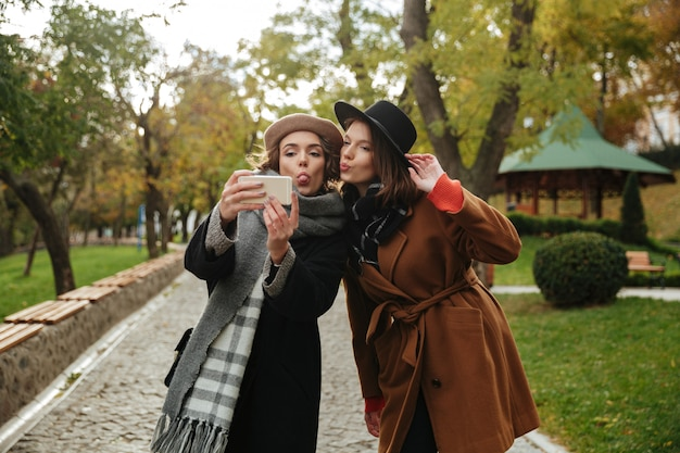 Un ritratto di due belle ragazze vestite in abiti autunnali