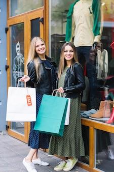 Un ritratto di due donne che stanno fuori del negozio che tiene i sacchetti della spesa variopinti