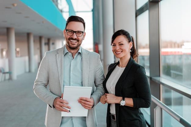 Un ritratto di due genti di affari che si levano in piedi nell'ingresso dell'ufficio.