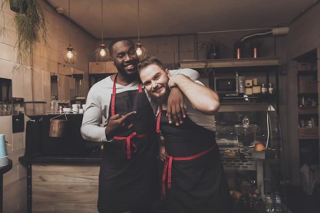 Un ritratto di due giovani baristi maschii all'area di lavoro